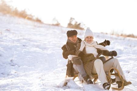 hombre con sombrero: Hermosa pareja senior en el trineo que se divierten, día de invierno.