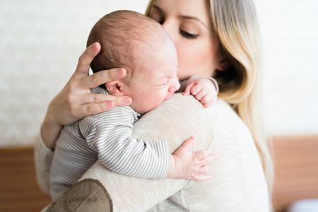 Mooie jonge moeder met zoontje in haar armen
