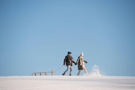 trineo: Hermosa pareja senior en un paseo que tiran del trineo, día de invierno.