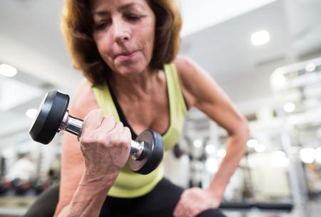 Hogere vrouw in gymnastiek die met gewichten uitwerkt. Stockfoto