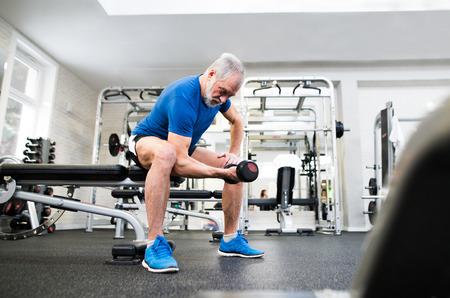 Senior man in de sportschool uit te werken met gewichten.