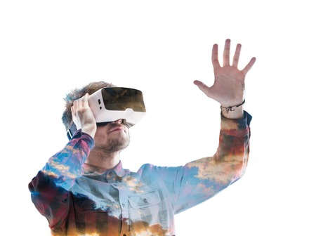 Double exposure. Man wearing virtual reality goggles. Sky.