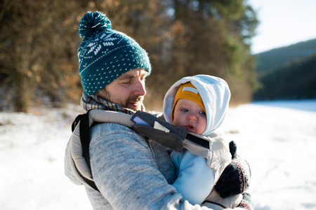 baby carrier: Father holding his son in baby carrier. Sunny winter nature.