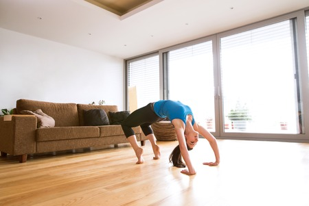 wooden floors: Young woman exercising at home, stretching, doing bridge pose.