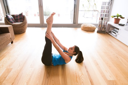 Young woman exercising at home, doing crunches.
