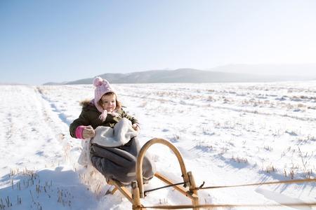 Cute little girl outside in winter nature, sitting on sledge