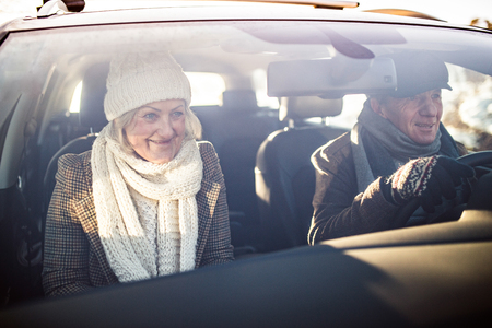 driving a car: Senior couple in winter clothes driving a car