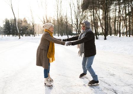 晴れた冬の自然のアイス スケートの年配のカップル。