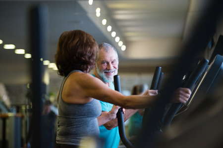 Beautiful fit senior couple in gym doing cardio work out. Stock Photo
