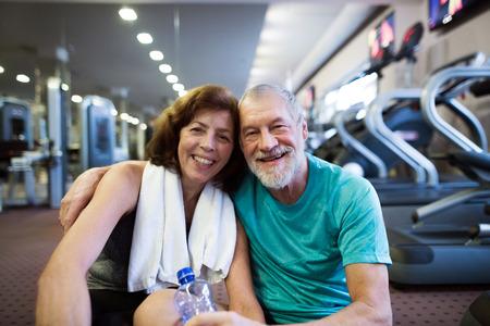 Ältere Paare in der Turnhalle vor Tretmühlen sitzen