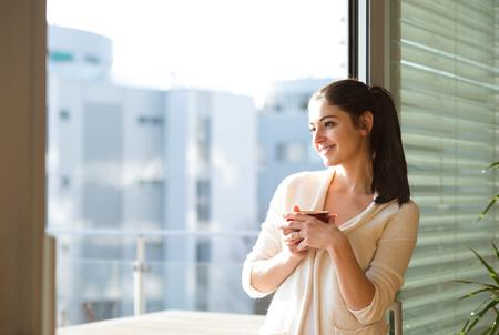 Frau entspannt auf dem Balkon, Tasse Kaffee oder Tee Standard-Bild - 69997239