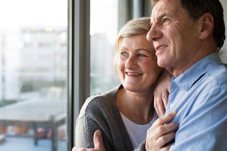 Pares mayores en la sala de estar de pie junto a la ventana, abrazando Foto de archivo