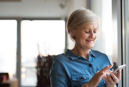 persona mayor: Senior woman with smartphone at home standing at the window