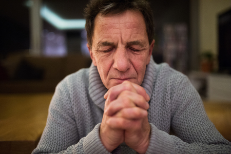 intercede: Senior man at home praying, hands clasped together