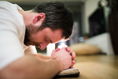 Young man praying, kneeling on the floor, hands on Bible Stock Photo