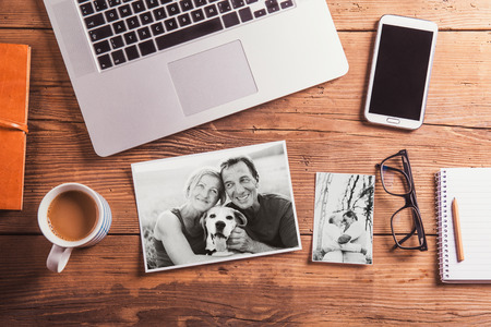 man dog: Office desk. Objects and black-and-white photos of senior couple