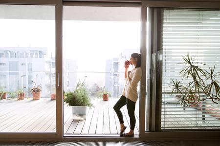 Donna che si distende sul balcone tenendo la tazza di caffè o tè