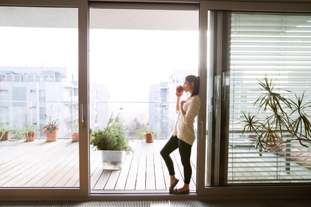 balcony window: Woman relaxing on balcony holding cup of coffee or tea Stock Photo