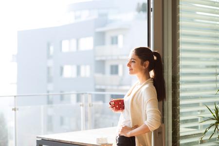 バルコニー持株カップ コーヒーまたは紅茶でリラックスできる女性