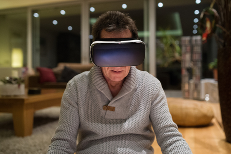 senior hombre con gafas de realidad virtual en el hogar