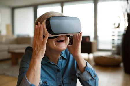 仮想現実を身に着けている年配の女性が自宅にゴーグルします。 写真素材