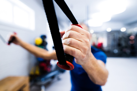 elastic band: Fit senior man in gym working out with weights.