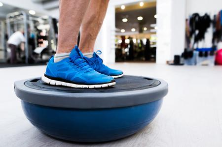 Hombre mayor irreconocible en el gimnasio de pie en la bola de equilibrio bosu