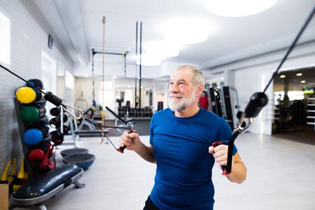 Fit senior man in de sportschool uit te werken met gewichten.