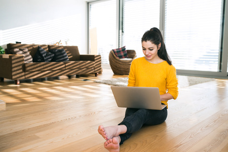 homeoffice: Woman at home sitting on the floor, working on laptop, writing