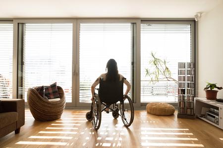 Jonge gehandicapte vrouw in rolstoel thuis, zicht naar achteren.