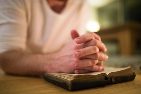 intercede: Unrecognizable man praying, kneeling on the floor, hands on Bibl