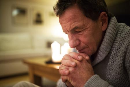 Senior man thuis bidden, brandende kaarsen achter hem.