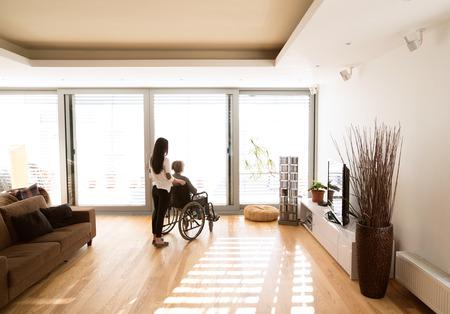 Gehandicapte hogere vrouw in rolstoel met haar jonge dochter. Stockfoto