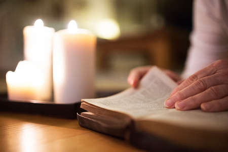 Unrecognizable woman reading Bible. Burning candles next to her.