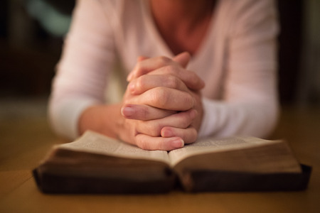 Unrecognizable woman praying, hands clasped together on her Bibl