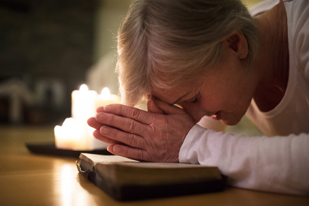 intercede: Senior woman praying, hands clasped together on her Bible.