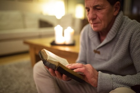intercede: Senior man at home reading Bible, burning candles behind him