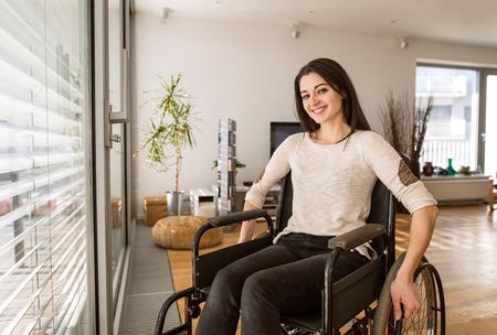 Joven mujer con discapacidad en silla de ruedas en casa en el salón.