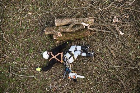 bucheron Injured avec tronçonneuse gisant sur le sol après la chute