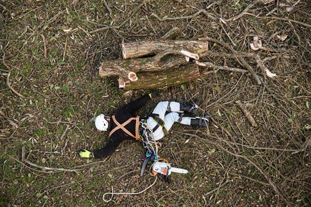 Injured lumberjack with chainsaw lying on the ground after fall Stock Photo