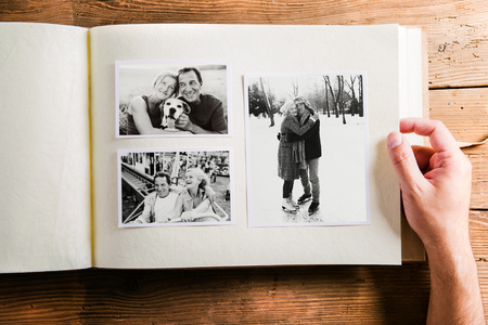 animal photo: Hand holding photo album with pictures of senior couple. Studio