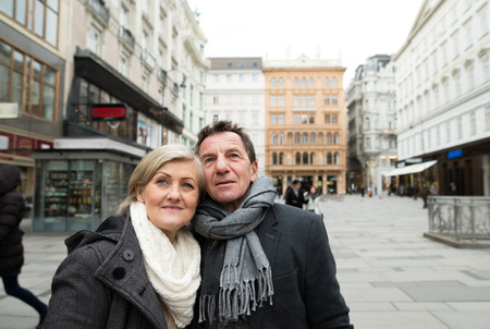 city centre: Beautiful senior couple on a walk in city centre. Winter. Stock Photo