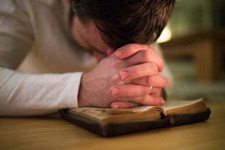 Homem irreconhecível orando, ajoelhado no chão, mãos na Bíblia