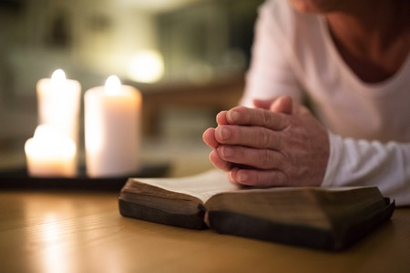 meditation help: Unrecognizable senior woman praying, hands clasped together on h Stock Photo