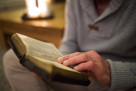 intercede: Unrecognizable man at home reading Bible, burning candles behind