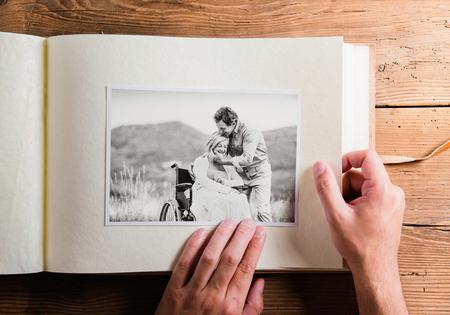 Mains tenant l'album photo avec la photo du couple de personnes âgées. Studio