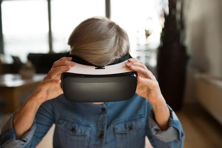 La mujer mayor que llevaba gafas de realidad virtual en el hogar
