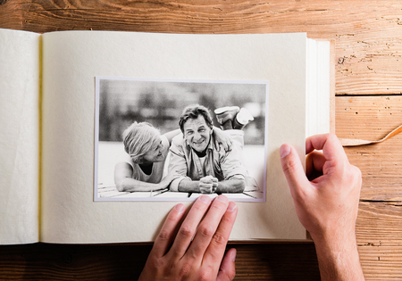 photo pictures: Hand holding photo album with pictures of senior couple. Studio