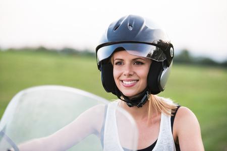 mujer rubia bonita que disfruta de un paseo en moto en el campo.