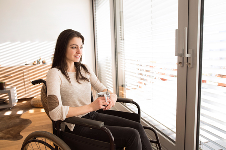 Beautiful young disabled woman in wheelchair at home. Imagens